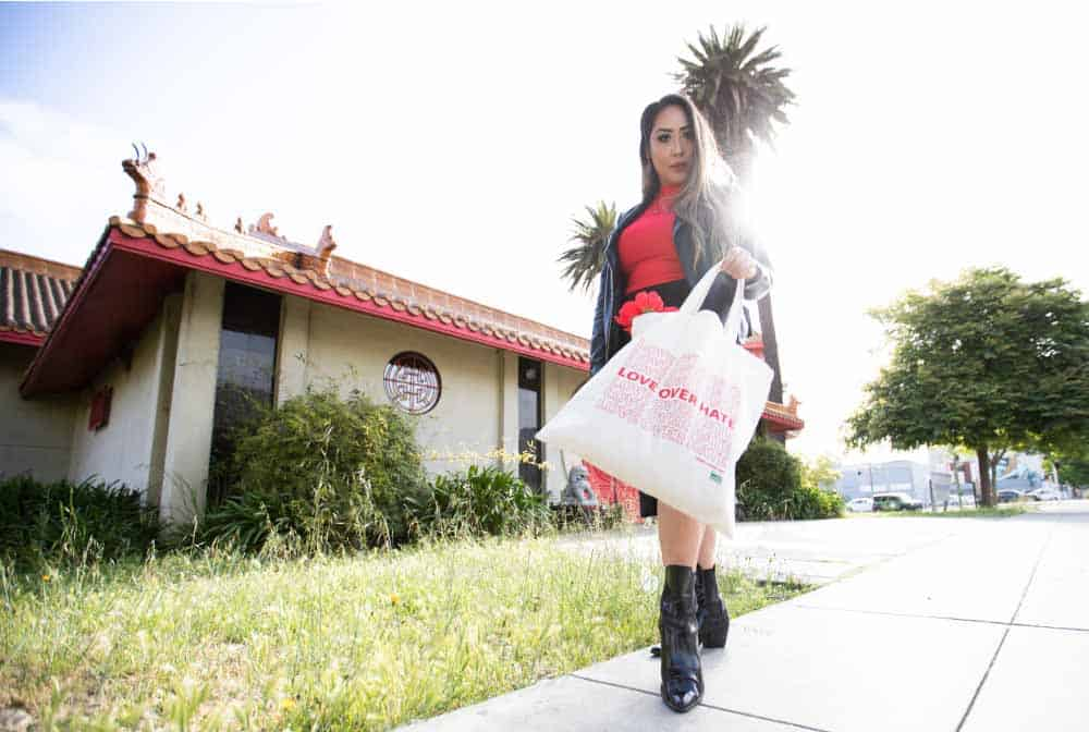 Asian woman holding bag that reads: Love Over Hate
