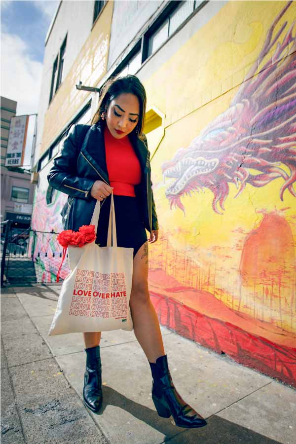 Asian woman holding tote bag that reads: Love Over Hate